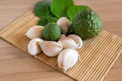 Κίτρο και σκόρδο στο χαλί makisu στην ξύλινη σύσταση στοκ εικόνες