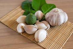 Κίτρο και σκόρδο στο χαλί makisu στην ξύλινη σύσταση στοκ εικόνα