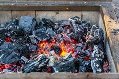 Καίγοντας άνθρακας στον ορειχαλκουργό σιδήρου προετοιμασία για τη σχάρα Εστία με τις πορτοκαλιές χοβόλεις στοκ εικόνες