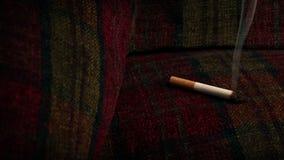 Καίγοντας καναπές τσιγάρων - έννοια κινδύνου πυρκαγιάς απόθεμα βίντεο