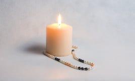 Καίγοντας κερί και στρογγυλές άσπρες χάντρες μαργαριταριών Στοκ φωτογραφία με δικαίωμα ελεύθερης χρήσης