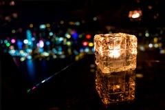 Καίγοντας κερί στο φλυτζάνι γυαλιού με το αφηρημένο υπόβαθρο Στοκ Εικόνες