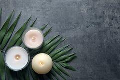 Καίγοντας κεριά κεριών και τροπικό φύλλο στο γκρίζο υπόβαθρο Στοκ φωτογραφία με δικαίωμα ελεύθερης χρήσης