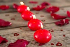 Καίγοντας κεριά που περιβάλλονται με τα αρωματικά ροδαλά πέταλα Στοκ Εικόνες