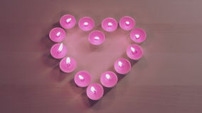 Καίγοντας κεριά που τοποθετούνται στη μορφή καρδιών απόθεμα βίντεο