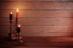 Καίγοντας κεριά στο εκλεκτής ποιότητας κηροπήγιο στο ξύλινο υπόβαθρο Στοκ φωτογραφίες με δικαίωμα ελεύθερης χρήσης