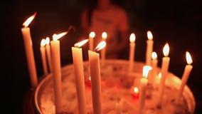 Καίγοντας κινηματογράφηση σε πρώτο πλάνο κεριών σε ένα κηροπήγιο εκκλησιών Ένα κορίτσι βάζει ένα κερί σε μας στο υπόβαθρο απόθεμα βίντεο
