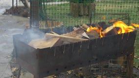 Καίγοντας ξύλο και άνθρακας στον ορειχαλκουργό Προετοιμασία της σχάρας shish kebab και σχάρα φιλμ μικρού μήκους