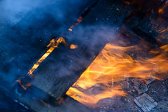 Καίγοντας ξύλο, φλόγα και καπνός στο μπλε υπόβαθρο Στοκ Φωτογραφίες