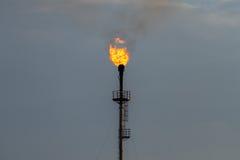 Καίγοντας φανός στις εγκαταστάσεις καθαρισμού ενάντια στον γκρίζο ουρανό στοκ φωτογραφία με δικαίωμα ελεύθερης χρήσης