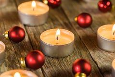 Καίγοντας φλόγες κεριών εμφάνισης με τις κόκκινες διακοσμήσεις σφαιρών Χριστουγέννων στοκ εικόνα