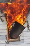 Καίγοντας φλόγες σπιτιών που βγαίνουν από ένα παράθυρο στοκ εικόνα με δικαίωμα ελεύθερης χρήσης