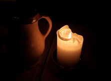 Καίγοντας φλυτζάνι κεριών και αργίλου της μπύρας στον πίνακα Στοκ Εικόνες