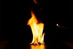 Καίγοντας φλόγα πυρκαγιάς στο μαύρο υπόβαθρο Στοκ Φωτογραφία