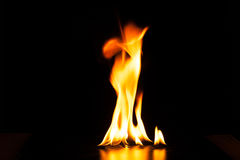 Καίγοντας φλόγα πυρκαγιάς στο μαύρο υπόβαθρο Στοκ Εικόνα