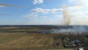 Καίγοντας χλόη κοντά στο χωριό απόθεμα βίντεο