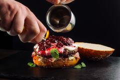 Καίγοντας burger αναφλέγεται με έναν αναπτήρα τσιγάρων και ποτίζεται με το ισχυρό οινόπνευμα Στοκ Εικόνες