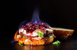 Καίγοντας burger, σάντουιτς χάμπουργκερ με cutlet του κιμά, brie τυριών, camembert, κεράσι μούρων Καίει, είναι Στοκ Εικόνα