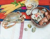 Καβούρι, θαλασσινά με τα μακαρόνια και κοχύλια στο εθνικό ύφασμα Στοκ φωτογραφία με δικαίωμα ελεύθερης χρήσης