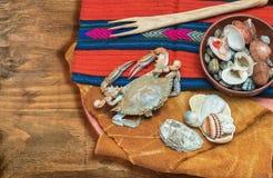 Καβούρι, θαλασσινά με το ξύλινο δίκρανο και κοχύλια στο εθνικό ύφασμα Στοκ φωτογραφίες με δικαίωμα ελεύθερης χρήσης
