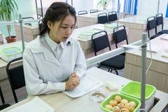 2019-09-01, Καζακστάν, Kostanay hydroponics Το ασιατικό κορίτσι σε ένα άσπρο παλτό μιλά για την ανάπτυξη των κρεμμυδιών σε ένα σχ στοκ εικόνες