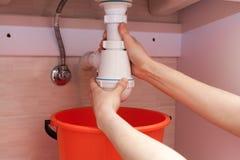 Καθάρισμα του παρεμποδισμένου σφυρηλατημένου μολυσμένου πλαστικού σιφωνίου του U για τη λεκάνη πλυσίματος, υγειονομικές συσκευές, Στοκ φωτογραφία με δικαίωμα ελεύθερης χρήσης