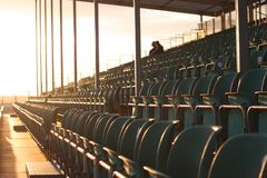 Καθίσματα εξεδρών επισήμων με δύο ανθρώπους στο φωτεινό ήλιο Στοκ Φωτογραφία