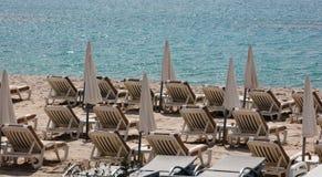 Καθίσματα και ομπρέλες παραλιών στην παραλία στην μπλε Μεσόγειο της νότιας Γαλλίας των Καννών Στοκ εικόνες με δικαίωμα ελεύθερης χρήσης
