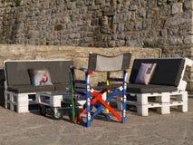 Καθίσματα και πίνακας που γίνονται από τις παλέτες στον τοίχο πετρών Στοκ φωτογραφία με δικαίωμα ελεύθερης χρήσης