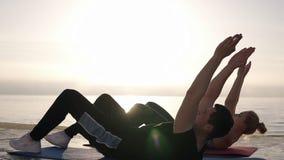Καθίστε το UPS - η άσκηση ζευγών ικανότητας κάθεται επάνω έξω στο μπροστινό thesea ή τον ωκεανό το καλοκαίρι Κατάλληλη ευτυχής επ φιλμ μικρού μήκους