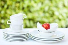 Καθαρά πιάτα και φλυτζάνια στο άσπρο τραπεζομάντιλο στο πράσινο υπόβαθρο Στοκ εικόνες με δικαίωμα ελεύθερης χρήσης