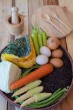 Καθαρά τρόφιμα, λαχανικά καθορισμένα, ξύλινο πιάτο και ξύλινο δίκρανο στον ξύλινο πίνακα Στοκ εικόνες με δικαίωμα ελεύθερης χρήσης