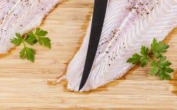 Καθαρές και καρυκευμένες λωρίδες ψαριών με το αιχμηρό μαχαίρι Στοκ εικόνα με δικαίωμα ελεύθερης χρήσης