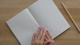 Καθαρές σελίδες ταλάντευσης χεριών γυναικών στο σημειωματάριο απόθεμα βίντεο
