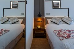 Καθαρή κρεβατοκάμαρα ξενοδοχείων με το φως κρεβατιών ανοικτό Στοκ Εικόνες