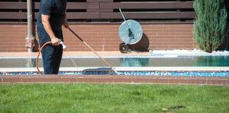Καθαρή πισίνα ατόμων με τη μάνικα στα χέρια υπαίθρια Στοκ Εικόνα