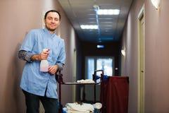 Καθαρίζοντας αίθουσα ξενοδοχείων ατόμων που φορά το μπλε παλτό Στοκ φωτογραφία με δικαίωμα ελεύθερης χρήσης