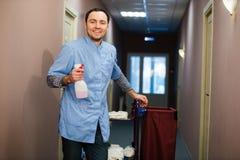 Καθαρίζοντας αίθουσα ξενοδοχείων ατόμων που φορά το μπλε παλτό Στοκ εικόνα με δικαίωμα ελεύθερης χρήσης