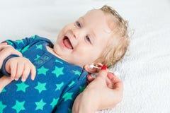 Καθαρίζοντας αυτί μωρών χεριών μητέρων και χαμόγελο μωρών Στοκ Φωτογραφία