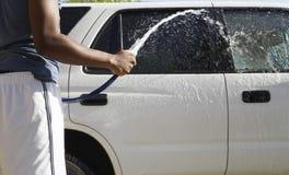 Καθαρίζοντας αυτοκίνητο ατόμων με τη μάνικα νερού Στοκ εικόνα με δικαίωμα ελεύθερης χρήσης