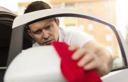 Καθαρίζοντας αυτοκίνητο ατόμων με το ύφασμα microfiber Στοκ εικόνα με δικαίωμα ελεύθερης χρήσης