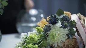 Καθαρίζοντας βάζο γυαλιού ανθοκόμων γυναικών στο υπόβαθρο, δέσμη λουλουδιών φιλμ μικρού μήκους