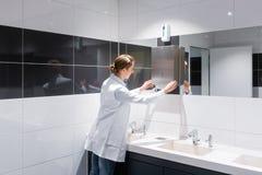 Καθαρίζοντας γυναίκα που ξαναγεμίζει την τουαλέτα πετσετών εγγράφου δημόσια στοκ φωτογραφία με δικαίωμα ελεύθερης χρήσης