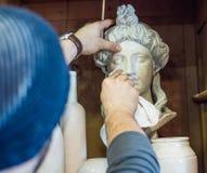 Καθαρίζοντας γλυπτά καλλιτεχνών/δασκάλων με ένα κομμάτι του υφάσματος - κλείστε αυξημένος στοκ εικόνες