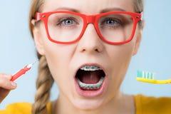 Καθαρίζοντας δόντια χαμόγελου γυναικών με τα στηρίγματα στοκ εικόνες με δικαίωμα ελεύθερης χρήσης