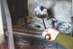 Καθαρίζοντας εστία φτυάρι εκμετάλλευσης χεριών με την τέφρα Στοκ Φωτογραφίες
