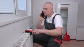 Καθαρίζοντας θερμαντικό σώμα υδραυλικών και ομιλία στο τηλέφωνο απόθεμα βίντεο