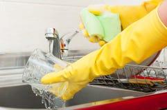 Καθαρίζοντας θηλυκό στο ξεπλένοντας γυαλί νερού κινηματογραφήσεων σε πρώτο πλάνο Στοκ Εικόνα