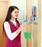 Καθαρίζοντας καθρέφτης γυναικών Brunette με το απορρυπαντικό Στοκ Φωτογραφία