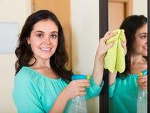Καθαρίζοντας καθρέφτης γυναικών Brunette Στοκ Φωτογραφία